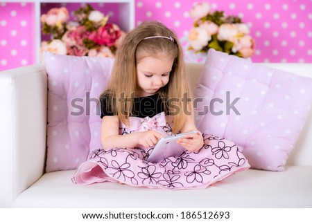Kid using modern tablet computers on white sofa in the polka-dot bright pink room at home fun game alone - stock photo