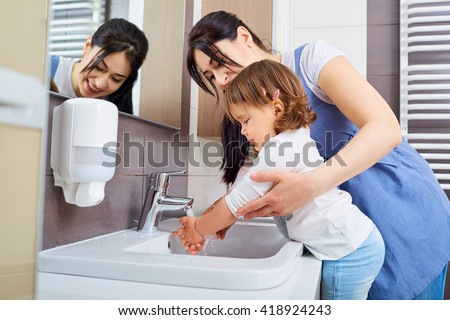 Kid washing hands with mom in the bathroom. - stock photo