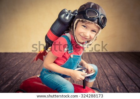 Kid with jet pack driving retro toy car. Child playing at home. Success, leader and winner concept - stock photo