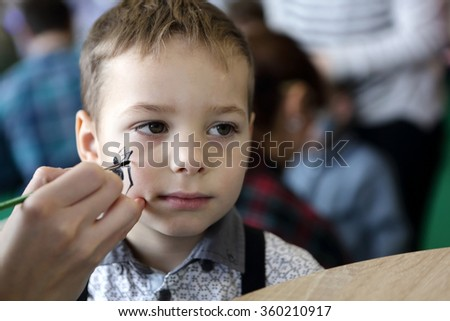 Kid with painting face at the amusement park - stock photo