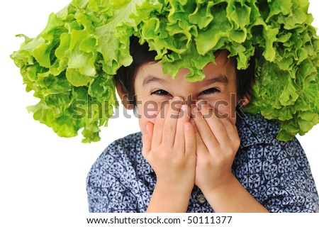 Kid with salad-hat on his head, laughing with hands on mouth - stock photo