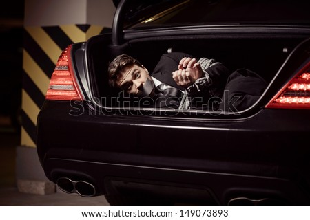 Kidnapped businessman. Tied up businessman lying in the car trunk and looking at camera - stock photo