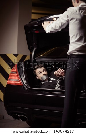 Kidnapped businessman. Tied up young man lying in the car trunk and looking at kidnapper - stock photo