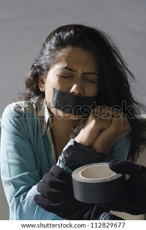 Kidnapper's hands wrapping adhesive tape around an abducted young woman's hands - stock photo
