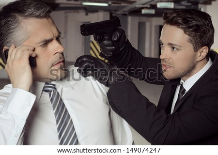 Kidnapper with gun. Aggressive young men with gun aiming businessman head while he is talking at phone - stock photo