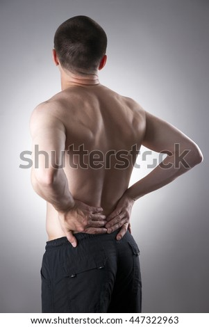 Kidney pain. Man with backache. Pain in the man's body on a gray background - stock photo