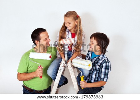 Kids and father with paint rollers and painting ladder - smiling happily - stock photo