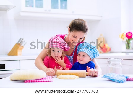Kids and mother baking. Two children and parent cooking. Little girl and baby boy cook and bake in a white kitchen with modern oven. Brother and sister in chef hats making a pie for dinner. - stock photo
