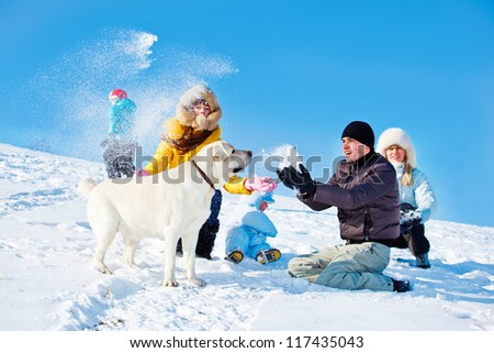 Kids and parents throwing snow on a winter hill - stock photo