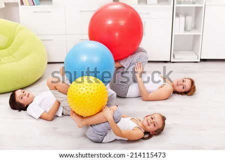 Kids and their mother exercising at home using large gymnastic balls - stock photo