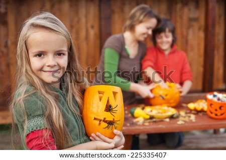 Kids and their mother preparing for Halloween - carving jack-o-lanterns - stock photo