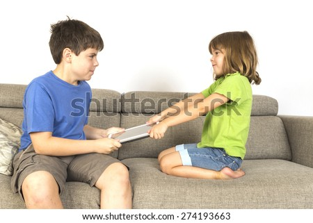 Kids arguing for playing with a digital tablet on a sofa.  - stock photo