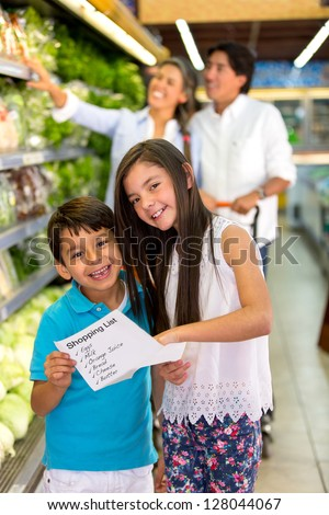 Kids at the supermarket holding a shopping list - stock photo