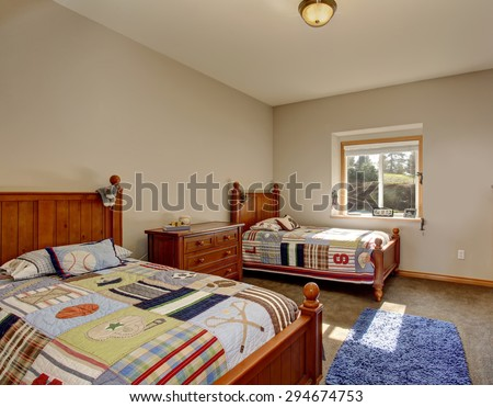 Kids' bedroom with twin beds, boy decor, and carpet. - stock photo