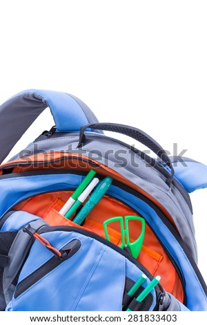 Kids blue and orange school backpack with pens and scissors stowed in the pockets for a creative art class, close up of the pockets and top of the bag over white - stock photo