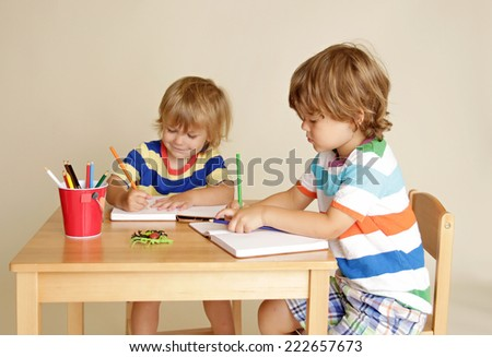 Kids, children engaged in art and craft with pencils and paper, learning and education concept - stock photo