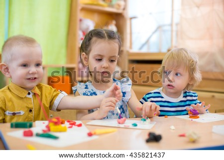 kids doing arts and crafts in day care kindergarten - stock photo
