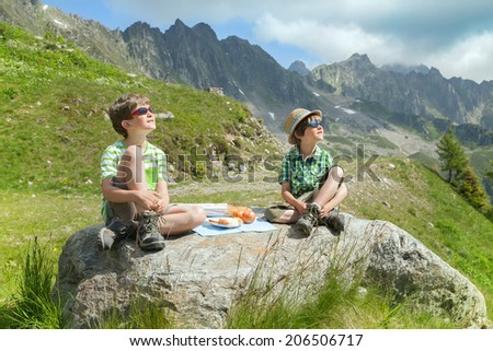kids eat cheese and bread during a hike in the mountains  - stock photo