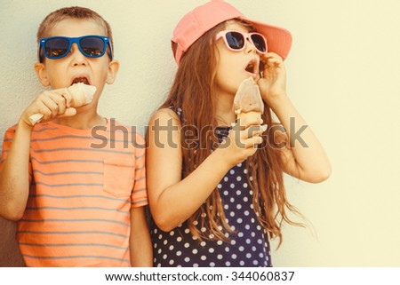 Kids eating gelato and soft serve ice cream. Boy and little girl in sunglasses enjoying summer holidays vacation. Instagram filter. - stock photo