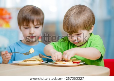kids eating healthy food at home or kindergarten - stock photo