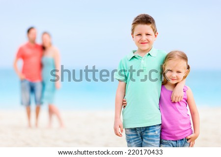 Kids embracing each other on tropical beach while parents standing on background - stock photo