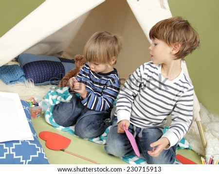 Kids engaged in arts and crafts activity, playing in a teepee tent at home - stock photo