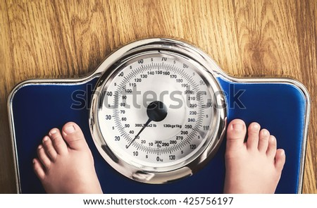 kids feet on weight scale - stock photo