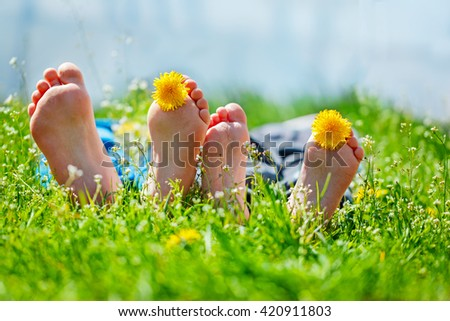 Kids feet with dandelion  flowers lying on green grass in sunny day. Concept happy childhood. - stock photo