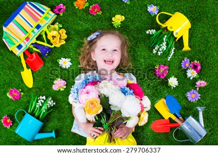 Kids gardening. Children with garden tools. Child with watering can and shovel. Little kid watering flowers. Girl relaxing on green backyard lawn in summer. - stock photo