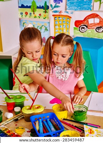 Kids girl painting at table in child school. - stock photo