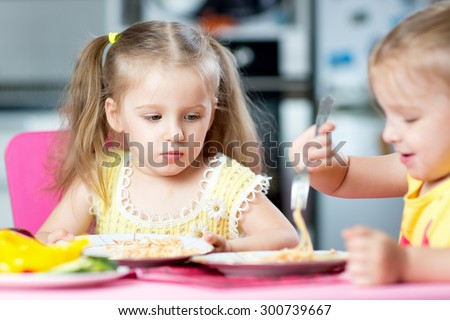 kids girls eating healthy food in kindergarten or at home - stock photo