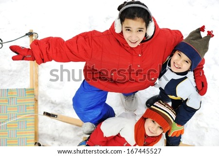Kids girls sitting in snow - stock photo