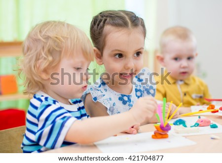 kids group doing arts and crafts in kindergarten - stock photo