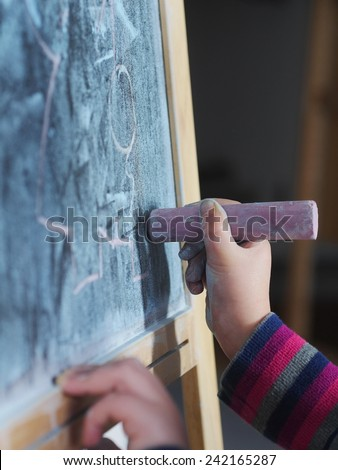kids hand holding a white chalk about to write - stock photo