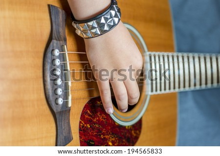 kids hand on a acoustic guitar, shallow depth of field - stock photo