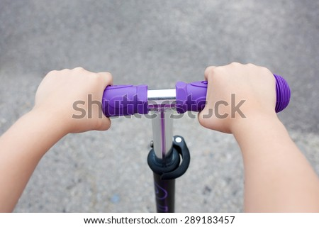 Kids hands holding handlebar on scooter or bicycle - stock photo