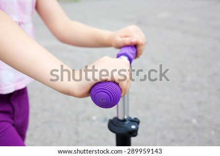 Kids hands holding handlebar on scooter or bicycle in an urban neighborhood - stock photo