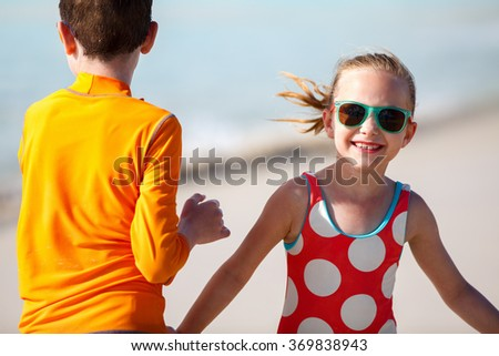 Kids having fun at tropical beach during Caribbean summer vacation playing together at shallow water - stock photo