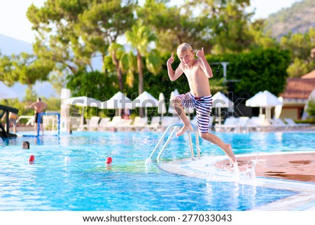 Kids having fun in summer. Happy active child, blonde caucasian teenage boy, jumping and diving into swimming pool in tropical resort at sunset - summertime vacation concept - stock photo