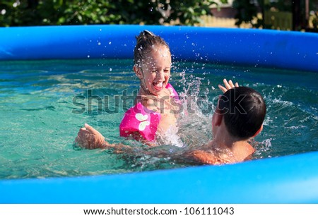 Kids having fun in the swimming pool - stock photo