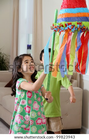 Kids hitting a pinata at birthday party - stock photo
