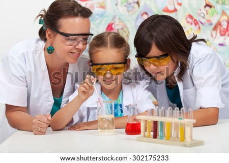 Kids in chemistry class with their teacher - doing a simple experiment - stock photo