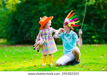 Kids in cowboy and cowgirl costumes playing outdoors. Children play with toy horse. Boy in Native American hat on Thanksgiving party. Toddler kid and school child during trick or treat at Halloween. - stock photo