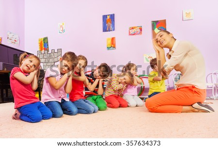 Kids in group play game pretending to sleep - stock photo