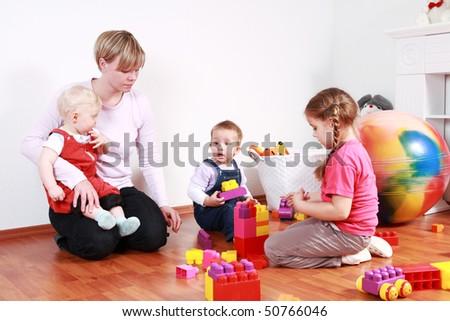 Kids in kindergarten with their teacher - stock photo