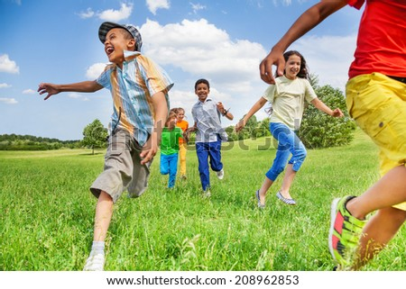Kids in motion of running on green field - stock photo