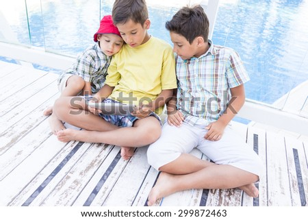 Kids in resort with tablet - stock photo