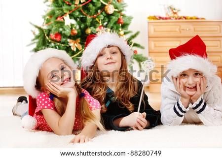 Kids in Santa hats lying on carpet - stock photo