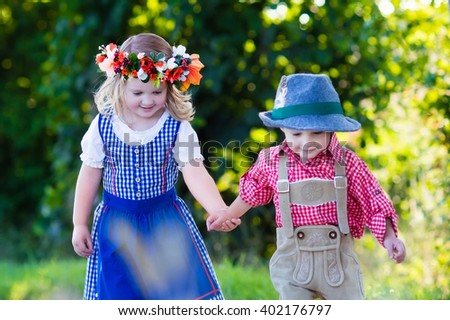 Kids in traditional Bavarian costumes in wheat field. German children eating bread and pretzel during Oktoberfest in Munich. Brother and sister play outdoors during autumn harvest time in Germany.  - stock photo