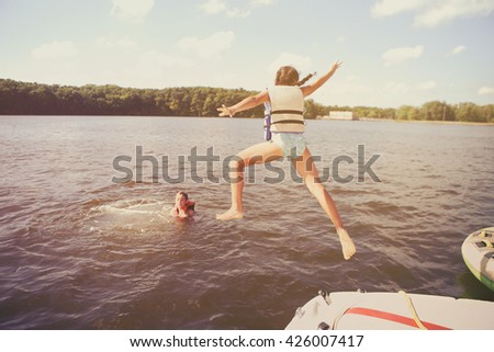 Kids jumping off a boat into the lake. Vintage Instagram effect. Some motion blur - stock photo